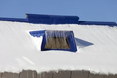 Snow-covered roof with icicles Royalty Free Stock Images