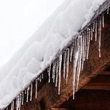 Snow covered roof with icicles. Bad weather, winter season concept, soft focus, shallow depth field. Snow covered roof with icicles. Bad weather, winter season Stock Image