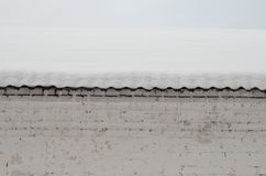 Snow-covered roof with icicles Royalty Free Stock Photo