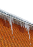 Snow-covered roof with icicles on white background Stock Photos