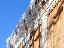 Snow-covered roof of old house with icicles Royalty Free Stock Image
