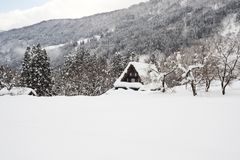 Snow covered roofed house Gassho-zukuri in Ainokura village, Gifu, Japan. Landscape in winter with snow falling on ground. With copy space Royalty Free Stock Photos