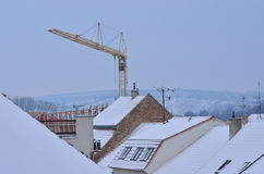Snow-covered roofs with chimneys, antennas and tower crane. Stock Images