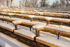 Snow-covered rows of benches in a park Royalty Free Stock Image
