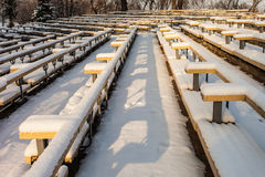 Snow-covered rows of benches in a park stock image