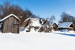 Snow-covered ruined courtyard in village in winter. Snow-covered old ruined courtyard in typical russian village in sunny winter day in Smolensk region of Russia Stock Photo
