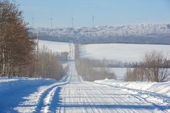 Snow covered rural road and wind turbines Stock Photos