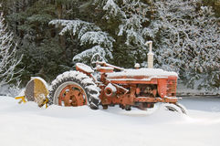 Snow covered rustic farm tractor. A old red farm tractor covered in fresh now next to a pine forest Royalty Free Stock Photography