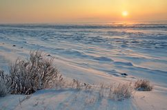 The snow-covered shore of lake Baikal at sunrise on a winter morning on the cape Bolshoy Kadilniy Royalty Free Stock Image