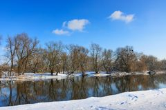 Snow-covered shore of small river against the blue sky stock photo