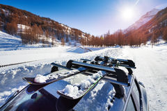 Snow-covered skis fastened on car roof rack Royalty Free Stock Photo