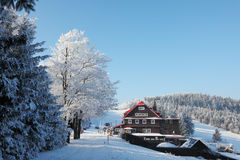 Snow-covered slope and a cozy ski hotel Stock Images