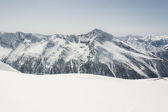 Snow covered slope with mountain ridge in the back Stock Images
