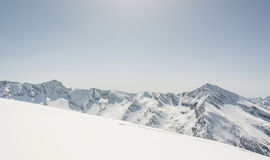 Snow covered slope with mountain ridge in the back Royalty Free Stock Photography