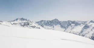 Snow covered slope with mountain ridge in the back Stock Photography