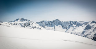 Snow covered slope with mountain ridge in the back Stock Photos