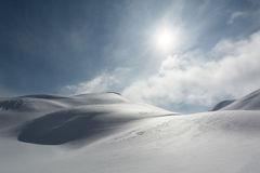 Snow covered slopes. Slopes covered in snow and sun shining through  misty clouds Stock Image