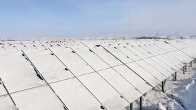 Snow-covered solar panels pan right stock video