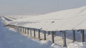Snow-covered solar panels on a sunny day pan view stock footage