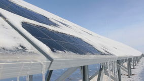 Snow-covered solar panels on a sunny day snow is melting drops flow stock video footage