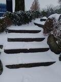 Snow covered stair steps without handrails for pedestrians with rocks and stones. On sides Royalty Free Stock Photos