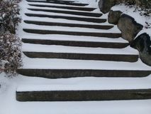 Snow covered stair steps without handrails for pedestrians. With rocks and stones on sides Stock Image