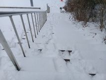 Snow covered stairs with stainless steel banister for pedestrians stock photography