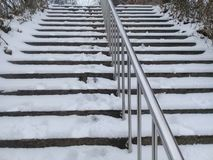 Snow covered stairs with stainless steel banister stock image
