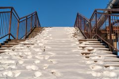 Snow covered stairs with stainless steel banister royalty free stock image