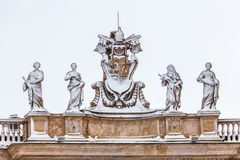 Snow-covered statues on the roof of St. Peter`s Cathedral in Vatican City in Rome in Italy Stock Images