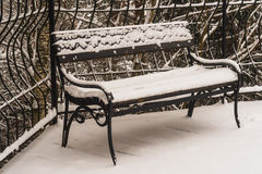 Snow-covered steel bench. Photo took  in Russia , photo is usable on picture post card, calendar, gardening, for wallpaper Stock Photo