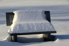 Snow covered stone bench Royalty Free Stock Image