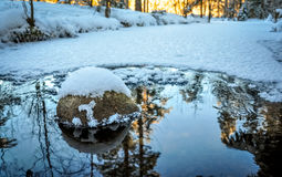 Snow-covered stone in the freezing water stream Royalty Free Stock Image