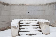 Snow-covered stone staircase near wall of old grey building with stock images
