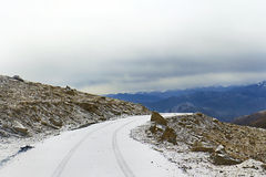 Snow-covered Straße auf einem Gebirgsdurchlauf Stockfotos
