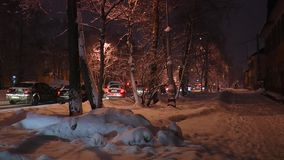 Snow-covered street with beautiful trees and snowdrifts and   passing vehicles in the light of the street lamps. stock footage