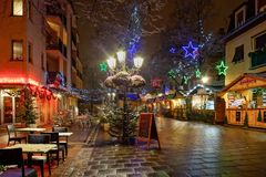 Snow-covered street cafe tables on winter street, Strasbourg, Ch. Ristmas time. Night scene with highlighted old buildings. Tourisitic concept. France Royalty Free Stock Photos