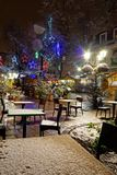 Snow-covered street cafe tables on winter street, Strasbourg, Ch. Ristmas time. Night scene with highlighted old buildings. Tourisitic concept. France Stock Image