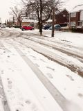 snow covered street road with tire tracks leading through village houses royalty free stock photography
