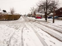 snow covered street road with tire tracks leading through village houses stock images