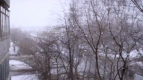 On snow-covered the street during a snowfall in slowmotion. Changes focus to forward in blurred. 1920x1080 stock video