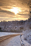 Snow covered street in sunrise in winter Stock Images