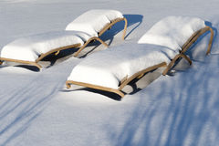 Snow covered sunbeds Stock Photo