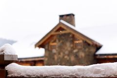 Snow-covered surface for product placement. Blurred house made of wood and stone on background. Snowfall on winter day. Christmas background with wooden royalty free stock photos