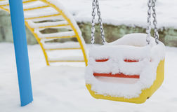 Snow covered swing at playground in winter Stock Images
