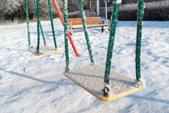 Snow covered swing and slide at playground in Royalty Free Stock Photos