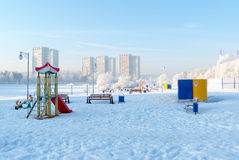 Snow covered swing and slide at playground in Stock Images