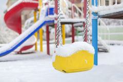 Snow covered swing and slide at playground in winter Stock Photos
