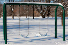 Snow Covered Swings. A photo of a swing set that is covered with snow. It was photographed in a park on a bright sunny day in winter Royalty Free Stock Images