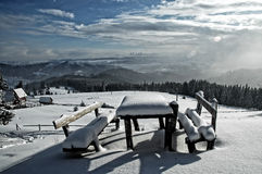 Snow covered table and benches in the mountains Stock Image